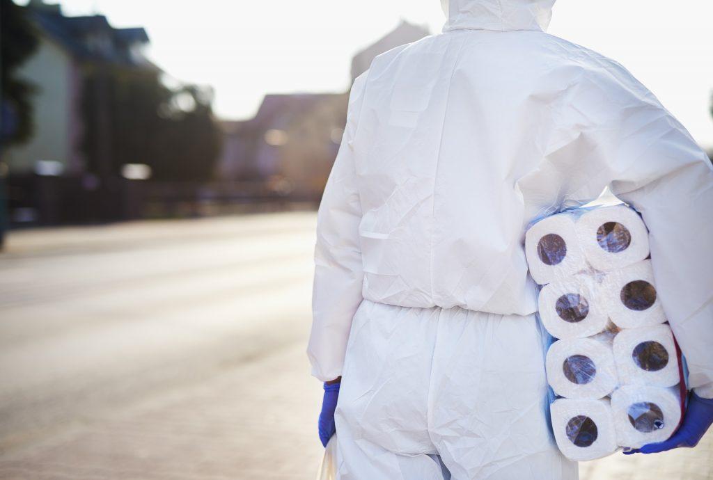 Kuvassa valkoiseen haalariin puettu henkilö kulkee vessapaperipaketti kainalossaan.