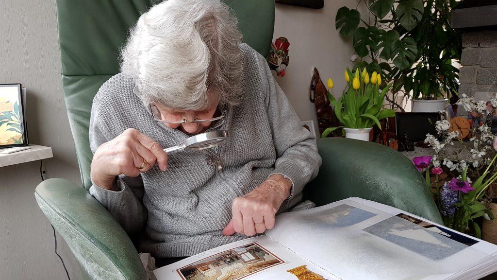 Vanha nainen tarkastelee suurennuslasilla valokuva-albumia