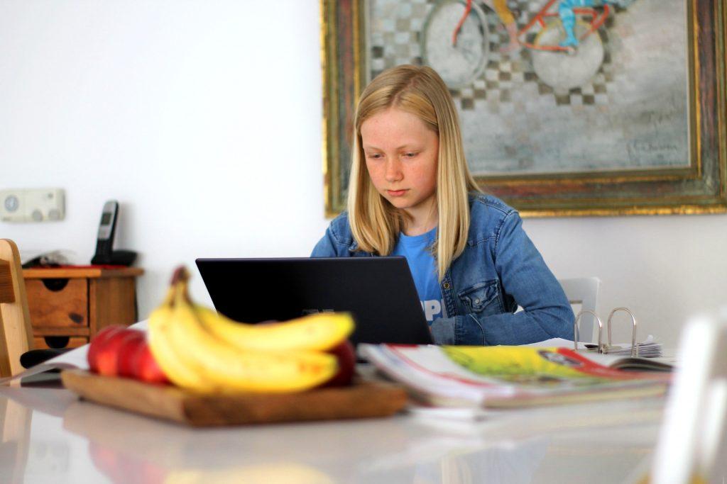 Tyttö tekee läksyjään kannettavalla tietokoneella, pöydällä on myös vihkoja ja hedelmiä.