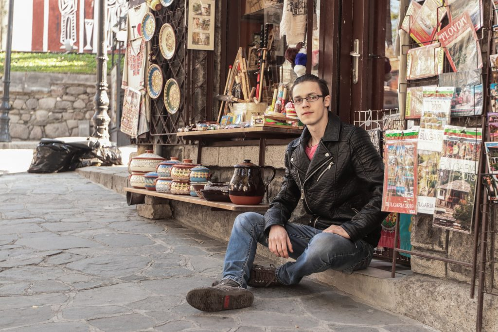 Nuori mies istuu kadulla kirjakaupan edessä.