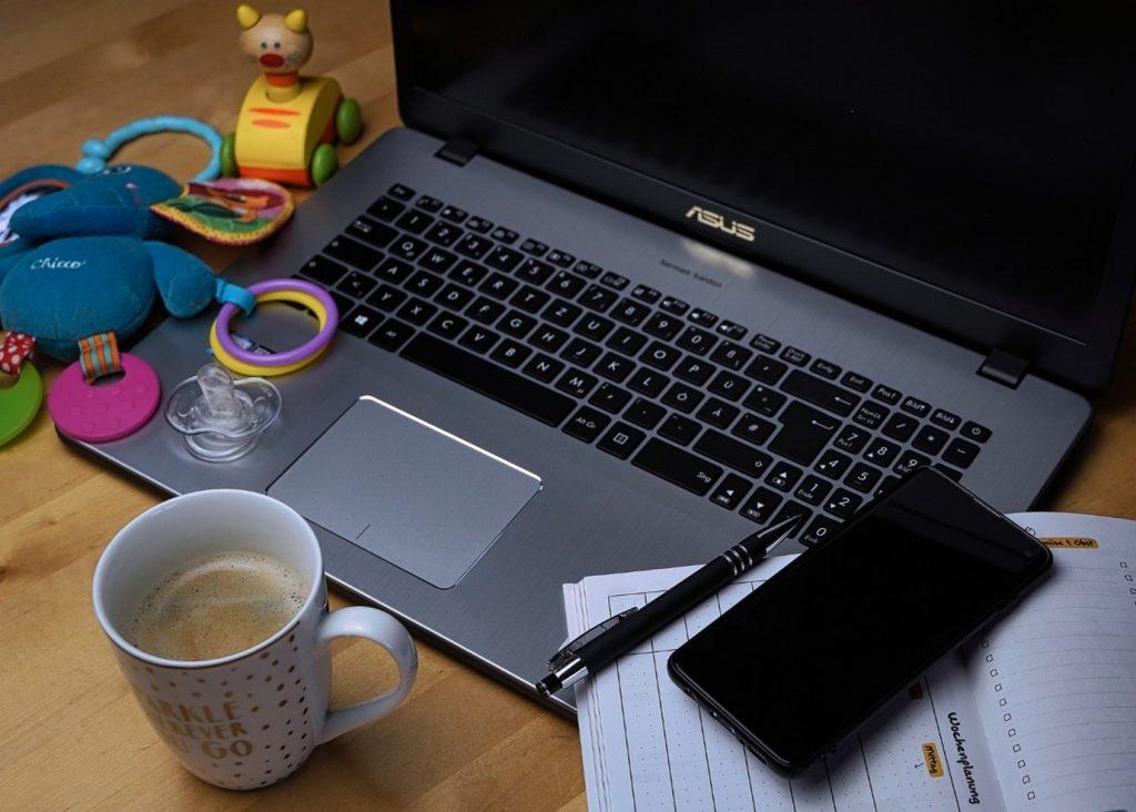 Pöydällä tietokone, kahvimuki, kalenteri ja leluja
