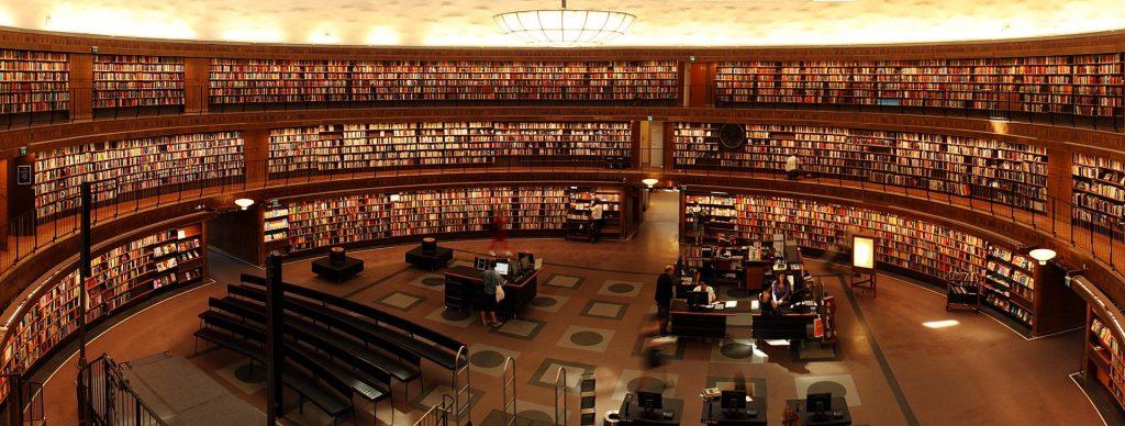 Pyöreä kirjastosali seinät täynnä hyllyjä.