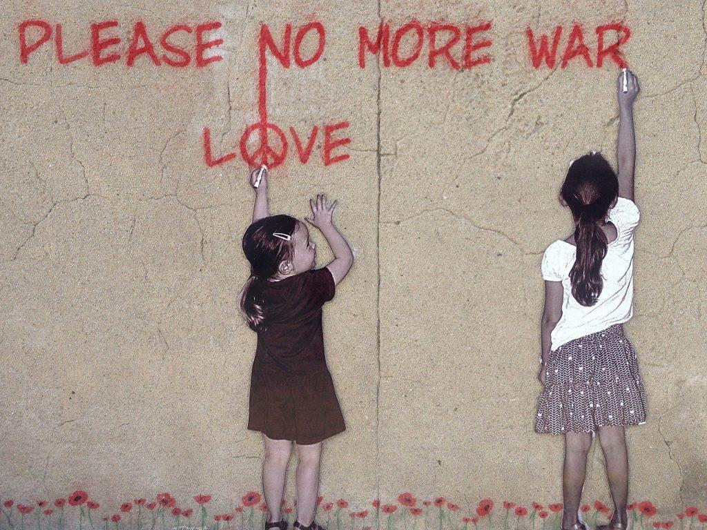 Tytöt piirtävät seinään love-not-war  -viestiä