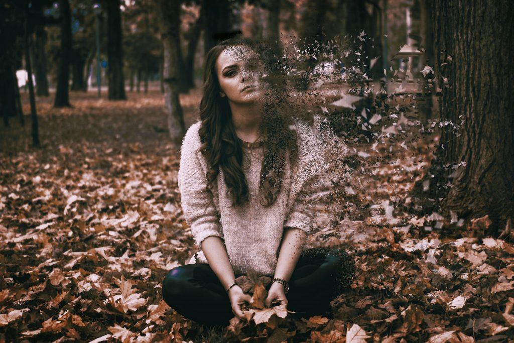 masentunut tyttö istuu metsässä.