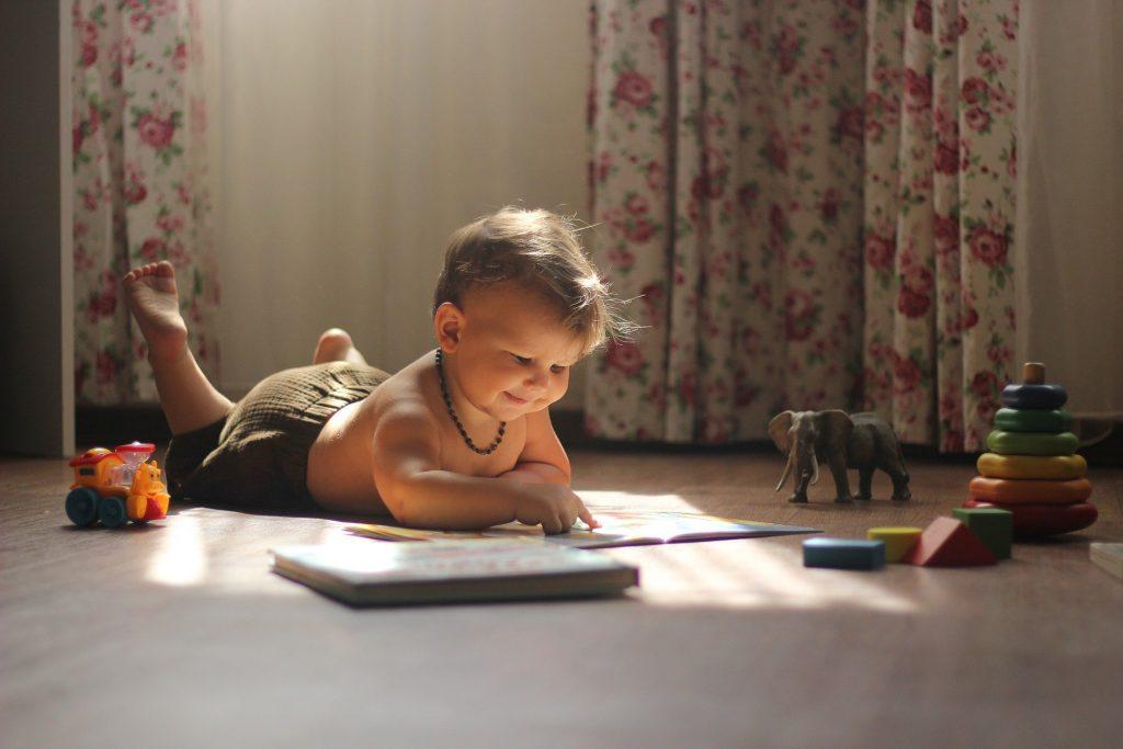 Lapsi lukee lattialla kuvakirjaa.