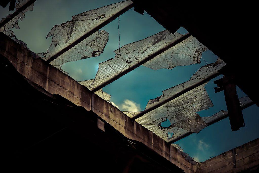 Särkyneiden lasien takaa siintää sininen taivas.