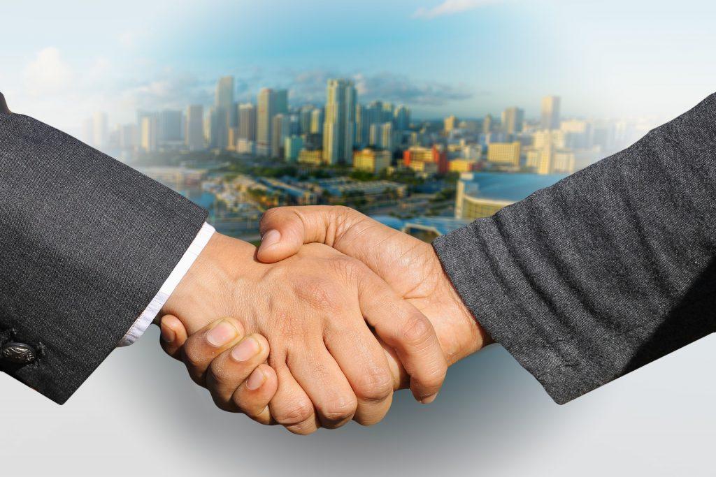 Kaksi henkilöä puristaa käsiä. Taustalla kaupungin silhuetti.