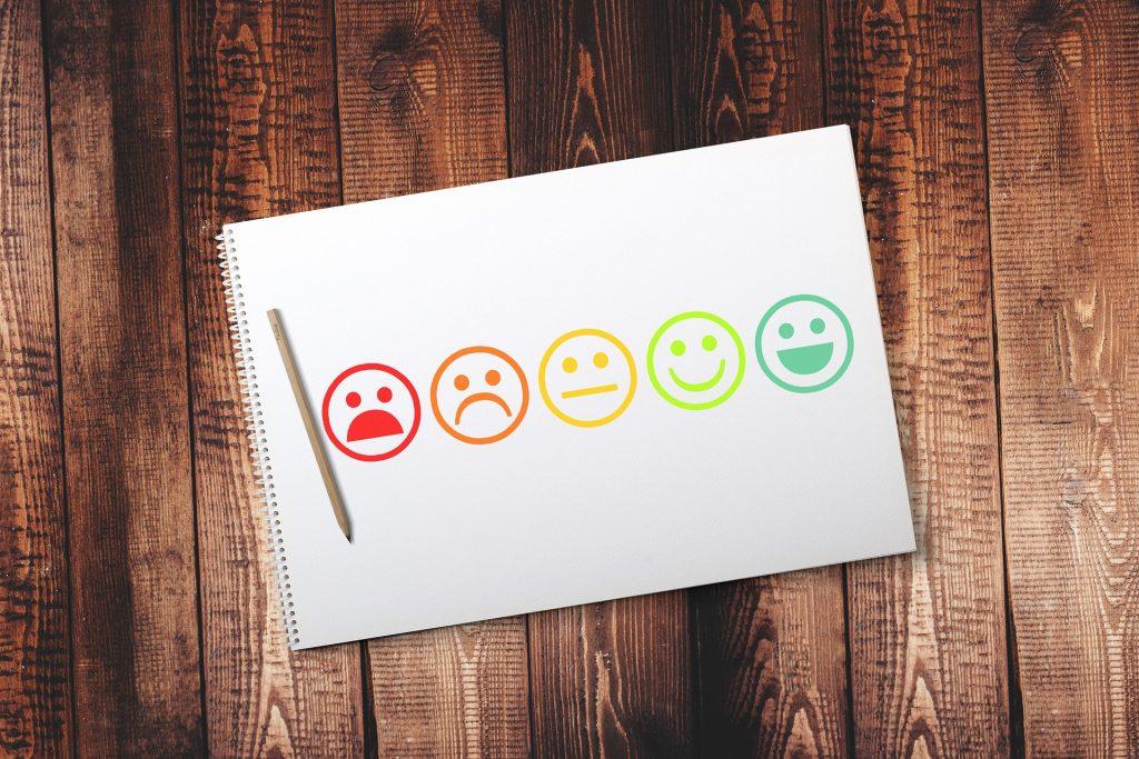 Lehtiö, kynä, lehtiössä arviointitehtävä, vaihtoehdot erittäin tyytymättömästä erittäin tyytyväiseen.