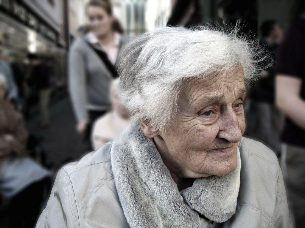 Vanha harmaapäinen nainen suvun keskellä.