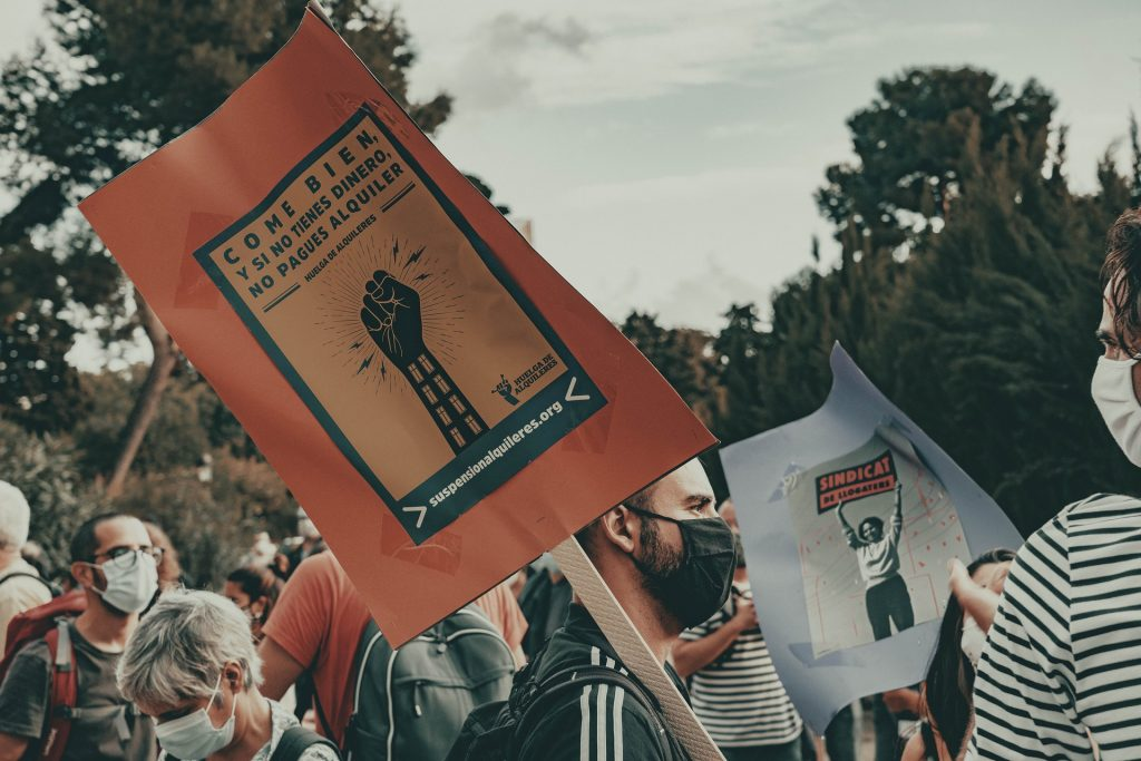 """Mielenosoittajia maskit päässä, julistessa teksti """"syö hyvin, ja jos et tienaa mitään, et maksa vuokraa"""""""