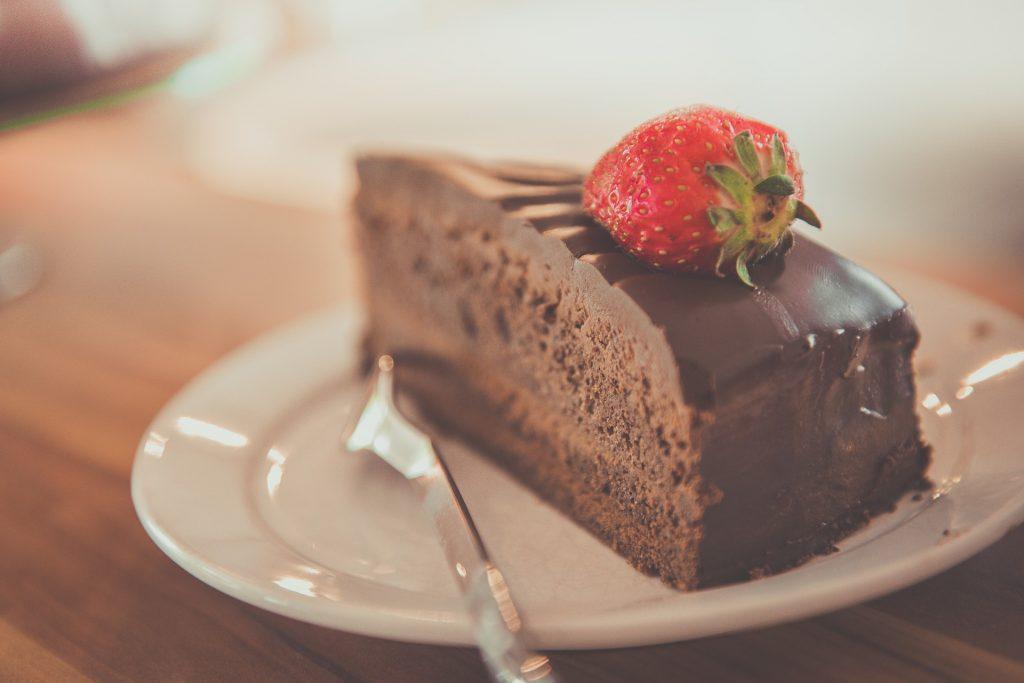 Mansikalla koristettu suklaakakku teevadilla, lusikka vieressä.