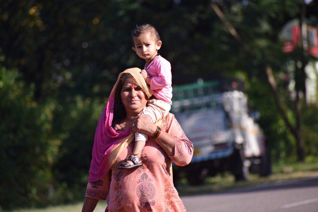 Intialainen isoäiti kantaa lapsenlastaan olkapäällään.