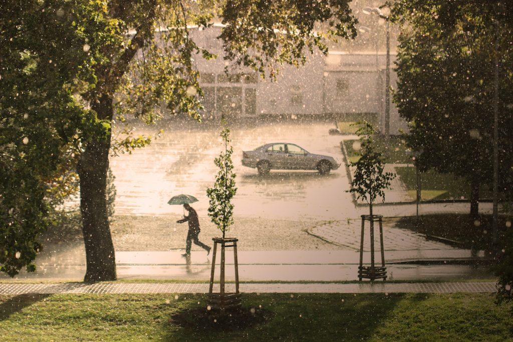 Yksinäinen auto tulvivalla parkkipaikalla.