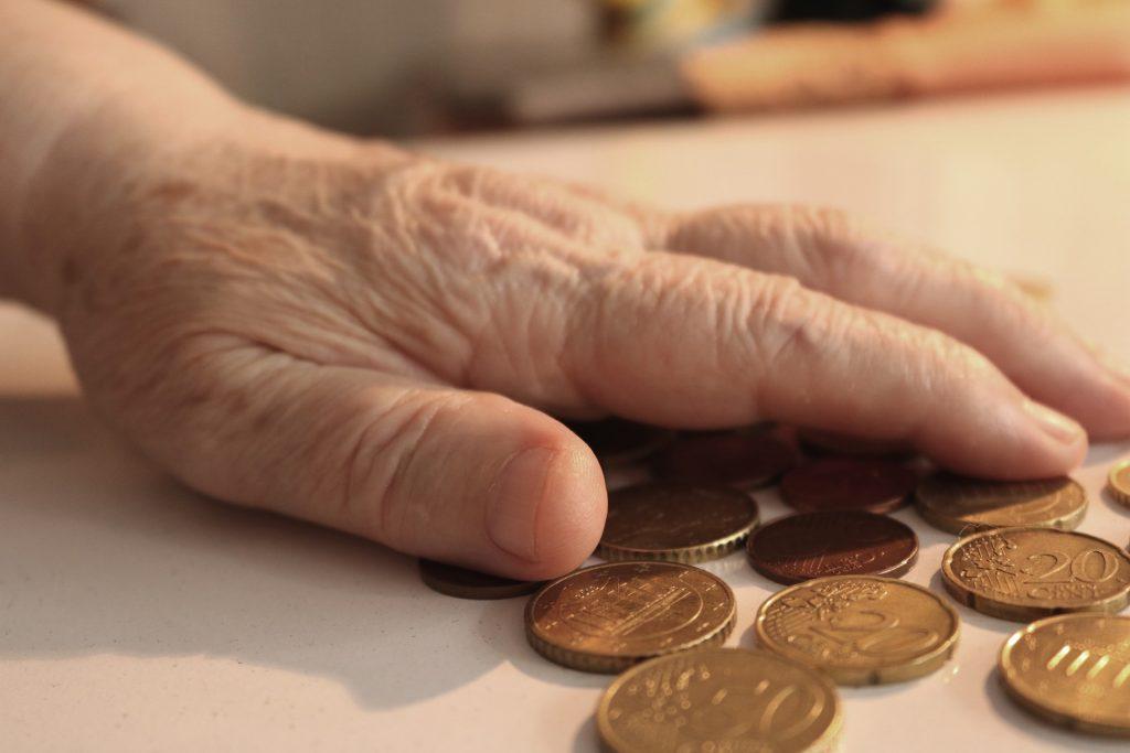 Vanhus laskee kolikoita.