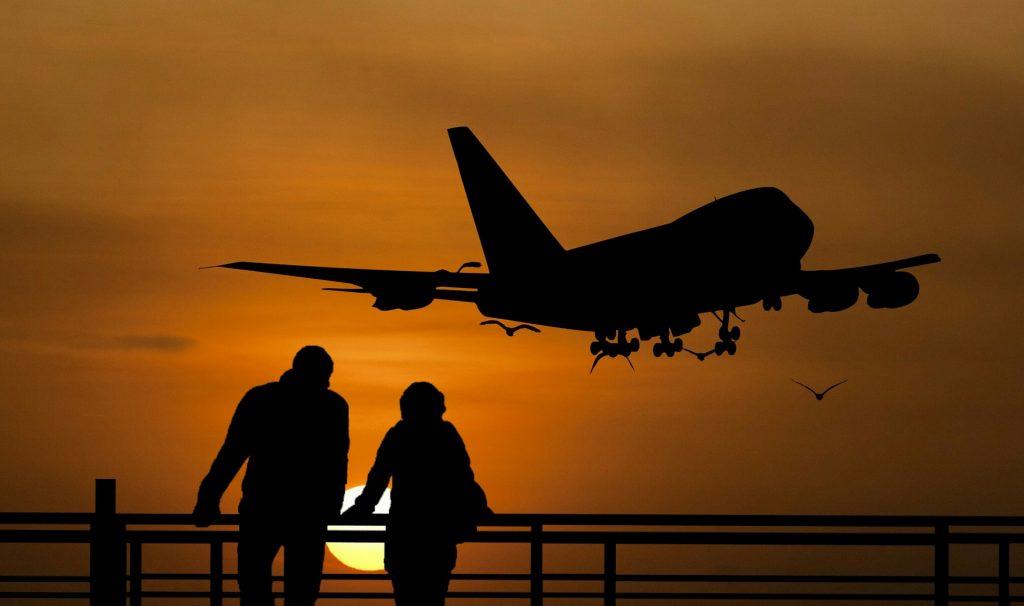 Vanha pariskunta lentokentällä, lentokone nousee ja aurinko laskee.