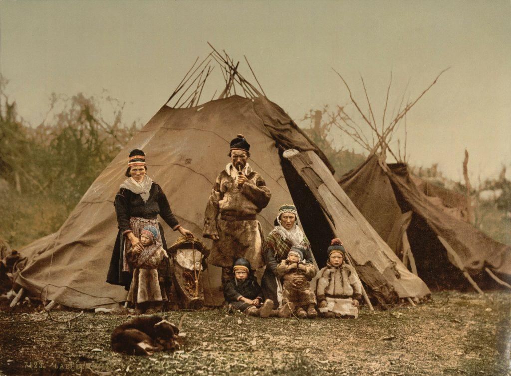 Saamelaisperhe perinteisissä asuissaan kodan edessä.