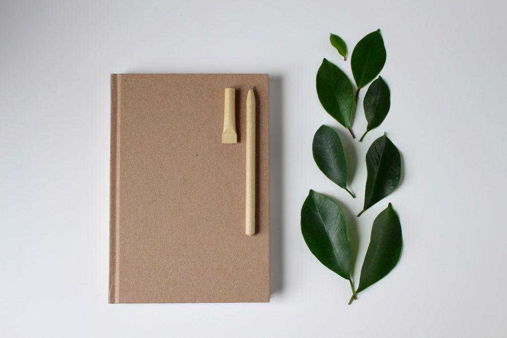 Uusiopaperista tehty muistilehtiö ja kynä.